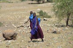 Mujeres que pertenecen a las tribus de Maasai que caminan en el arbusto Imagen de archivo