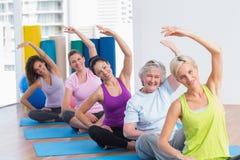 Mujeres que practican estirando ejercicio en clase del gimnasio Foto de archivo libre de regalías