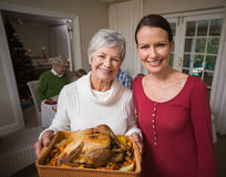 Mujeres que presentan con el pavo de la carne asada delante de su familia Fotografía de archivo libre de regalías