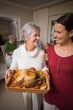 Mujeres que presentan con el pavo de la carne asada delante de su familia Imagenes de archivo