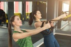Mujeres que realizan el entrenamiento de la suspensión de TRX en gimnasio fotografía de archivo