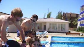 Mujeres que reciben masaje de sus novios en un chalet hermoso por la piscina Tiro a cámara lenta almacen de metraje de vídeo