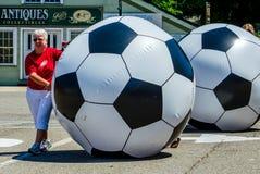 Mujeres que ruedan balones de fútbol gigantes Fotografía de archivo