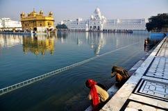 Mujeres que ruegan en el templo de oro Amritsar Imágenes de archivo libres de regalías