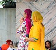 Mujeres que ruegan en el templo de oro en Amritsar, la India Imagenes de archivo