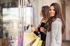 Mujeres que se colocan delante de una tienda de ropa Fotos de archivo
