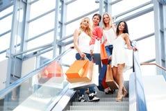 Mujeres que se colocan en la escalera móvil Imágenes de archivo libres de regalías