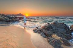 Mujeres que se colocan en la playa arenosa en la salida del sol hermosa Fotografía de archivo libre de regalías
