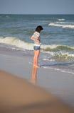 Mujeres que se colocan en la playa del mar y que miran al mar Fotos de archivo
