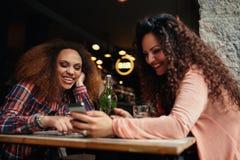 Mujeres que se divierten usando un teléfono elegante en café Imagen de archivo libre de regalías