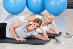 Mujeres que se relajan en las esteras de la gimnasia Imágenes de archivo libres de regalías
