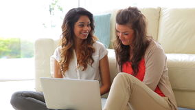Mujeres que se sientan delante del sofá con el ordenador portátil almacen de video