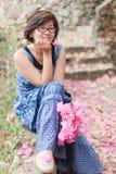 Mujeres que se sientan en la manera en jardín Fotografía de archivo libre de regalías