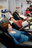 Mujeres que se sientan en una silla del masaje Imagen de archivo libre de regalías