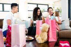 3 mujeres que sonríen en un bebé rodeado por los regalos Fotos de archivo