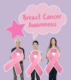Mujeres que sostienen cintas de la conciencia del cáncer de pecho foto de archivo libre de regalías
