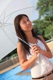 Mujeres que sostienen el paraguas blanco adentro al lado de la natación po Imagenes de archivo