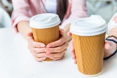 Mujeres que sostienen las tazas de café en manos Fotos de archivo libres de regalías