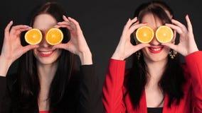 Mujeres que sostienen naranjas partidas en dos delante de sus ojos almacen de metraje de vídeo