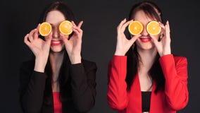 Mujeres que sostienen naranjas partidas en dos delante de sus ojos metrajes
