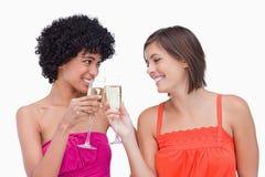 Mujeres que tintinean los vidrios de champán Imágenes de archivo libres de regalías