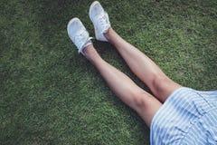 Mujeres que tocan en las piernas con la lona blanca Fotografía de archivo