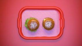 Mujeres que toman el cheeseburger y el bocadillo vegetariano de la bandeja plástica, almuerzo almacen de metraje de vídeo
