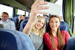 Mujeres que toman el selfie por smartphone en autobús del viaje Foto de archivo libre de regalías