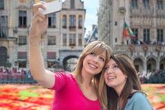 Mujeres que toman un autorretrato con smartphone contra la carpa de la flor Fotos de archivo