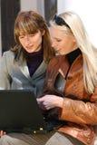 Mujeres que trabajan con la computadora portátil en parque de la ciudad Imagenes de archivo