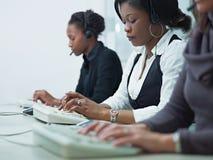 Mujeres que trabajan en centro de atención telefónica Imagen de archivo libre de regalías