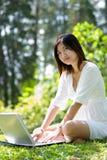 Mujeres que trabajan en la computadora portátil Imágenes de archivo libres de regalías