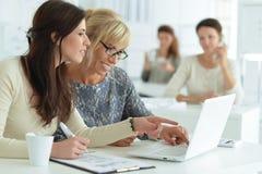 Mujeres que trabajan junto en oficina Foto de archivo libre de regalías