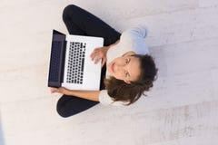 Mujeres que usan el ordenador portátil en la opinión superior del piso Fotos de archivo libres de regalías
