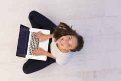 Mujeres que usan el ordenador portátil en la opinión superior del piso Foto de archivo
