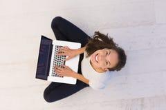 Mujeres que usan el ordenador portátil en la opinión superior del piso Foto de archivo libre de regalías