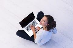 Mujeres que usan el ordenador portátil en la opinión superior del piso Imágenes de archivo libres de regalías