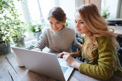 Mujeres que usan el ordenador portátil en restaurante Fotografía de archivo