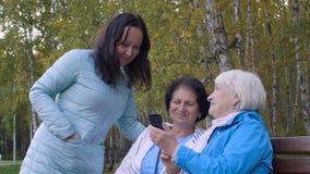Mujeres que usan el teléfono móvil y riendo en paisaje del parque del otoño almacen de metraje de vídeo
