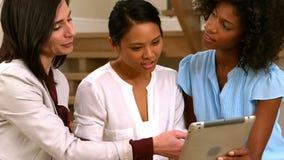 Mujeres que usan la tableta junto almacen de metraje de vídeo