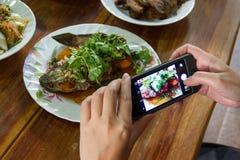 Mujeres que usan los teléfonos móviles para tomar imágenes Foto de archivo libre de regalías