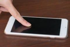 Mujeres que usan smartphone en la tabla de madera Imágenes de archivo libres de regalías