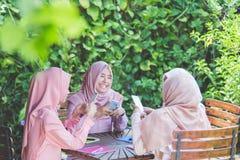Mujeres que usan su propio smartphone mientras que se sienta en un café Fotografía de archivo