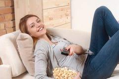 Mujeres que ven la TV con palomitas en casa en la sala de estar foto de archivo