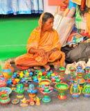 Mujeres que venden artículos coloridos de la cerámica en ella parada Imágenes de archivo libres de regalías