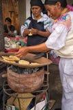 Mujeres quechuas que preparan el flatbread en el disco de cerámica en Ecuador Fotos de archivo