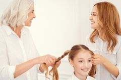 Mujeres radiantees que sonríen mientras que hace las colas de caballo para la niña Foto de archivo libre de regalías