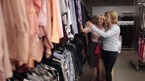 Mujeres rubias felices que miran a través de la ropa en el estante almacen de metraje de vídeo