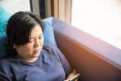 Mujeres 40s de Asia que sostienen el smartphone que piensa en el sofá Imagen de archivo