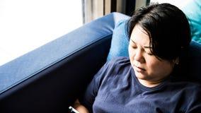 Mujeres 40s de Asia que sostienen el smartphone que piensa en el sofá Imagenes de archivo
